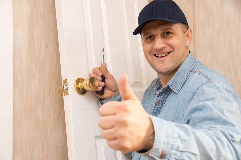 A locksmith technician working on a residential properties' locks.